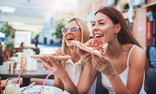 Pizza time. Handsome smiling women eating pizza, having fun together in the restaurant. Consumerism, food, lifestyle concept