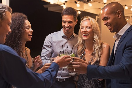 Group of young multiethnic friends enjoying evening and drinking cocktails. Happy men and women raising a toast with mojito on a patio under the light bulb wire. Elegant girls and stylish guy having fun together at party night.
