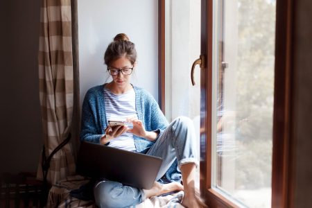 Young woman working from home office. Freelancer using laptop, phone and the Internet. Workplace in living room on windowsill. Concept of female business, career, shopping online. Lifestyle moment.