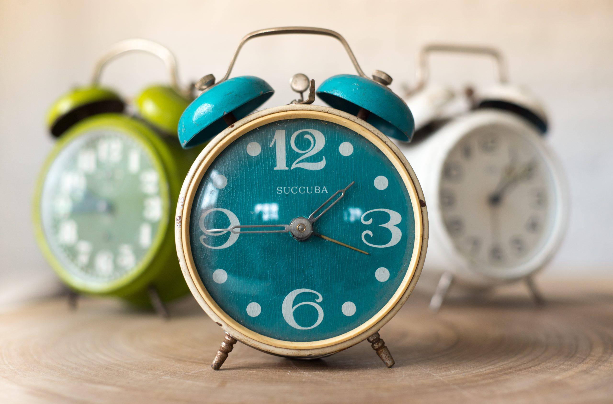 three retro alarm clocks