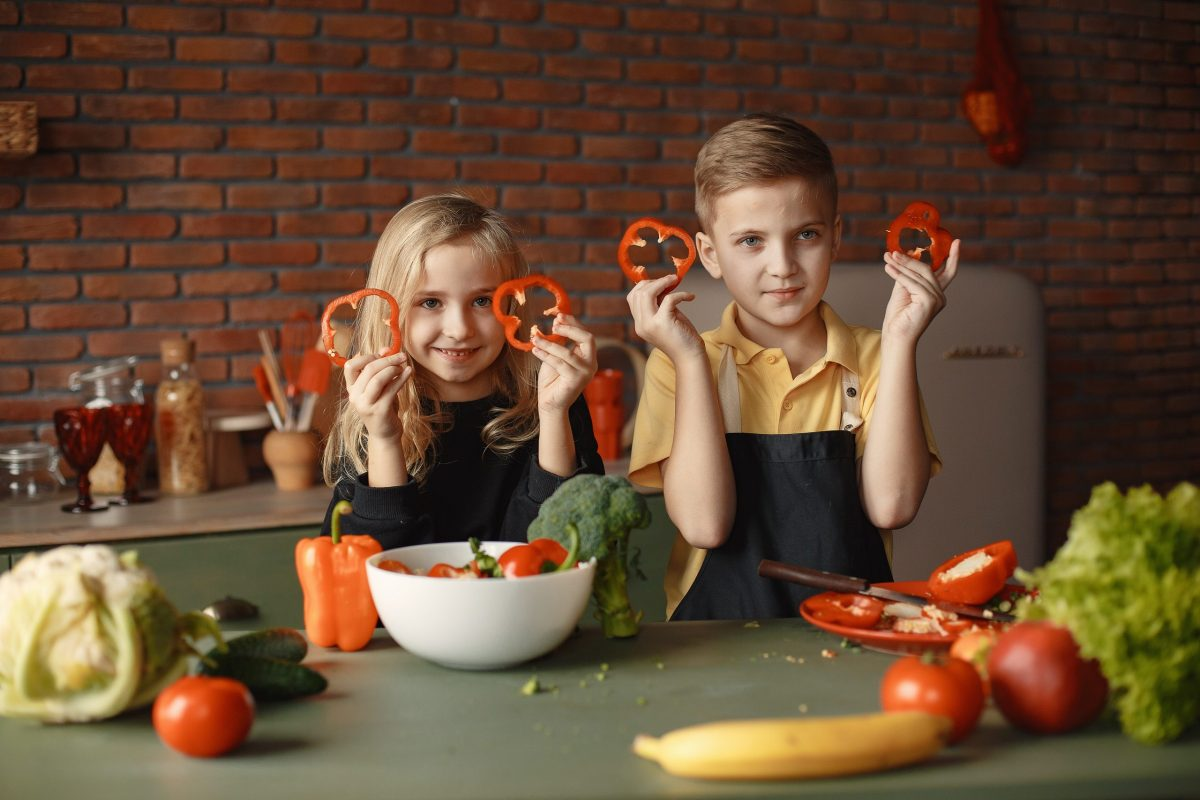 Children in the Kitchen Holding Slices of Capsicum.