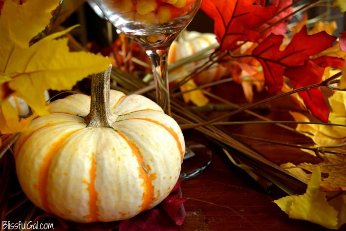 Creating a quick and easy fall centerpiece with wine glasses, candy corn, and leaves is perfect for fall