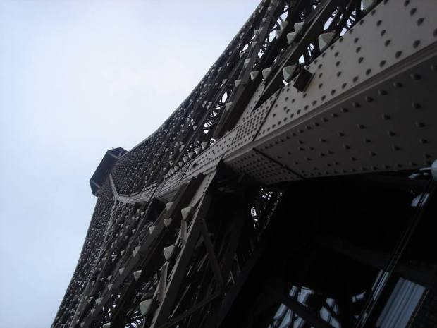 From the ground, the view to the top of the Eiffel Tower in Paris.