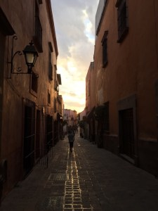 Moving to Mexico: A picture of a long cobblestone style walkway between two buildings, around sunset. Clouds are blocking the sun.