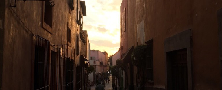 A picture of a long cobblestone style walkway between two buildings, around sunset. Clouds are blocking the sun.