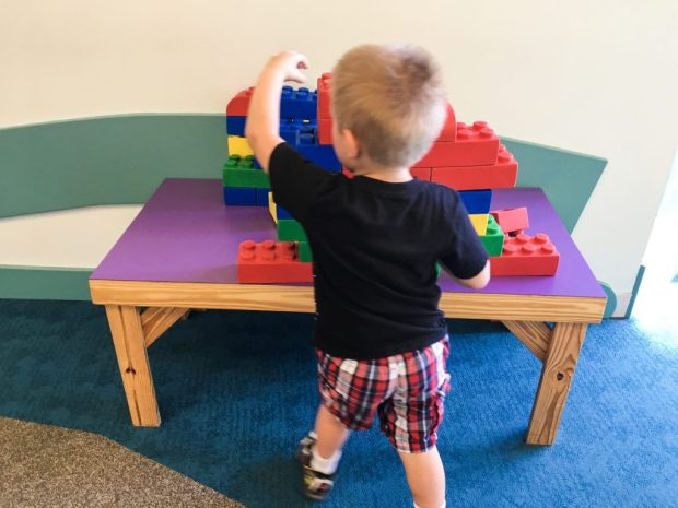 a child playing with larger than normal lego pieces.
