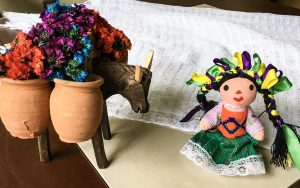 A wooden donkey carrying terra-cotta pots filled with artificial flowers, a doll with green, yellow, and purple bows in her black hair, and a white scarf apparently from Oaxaca