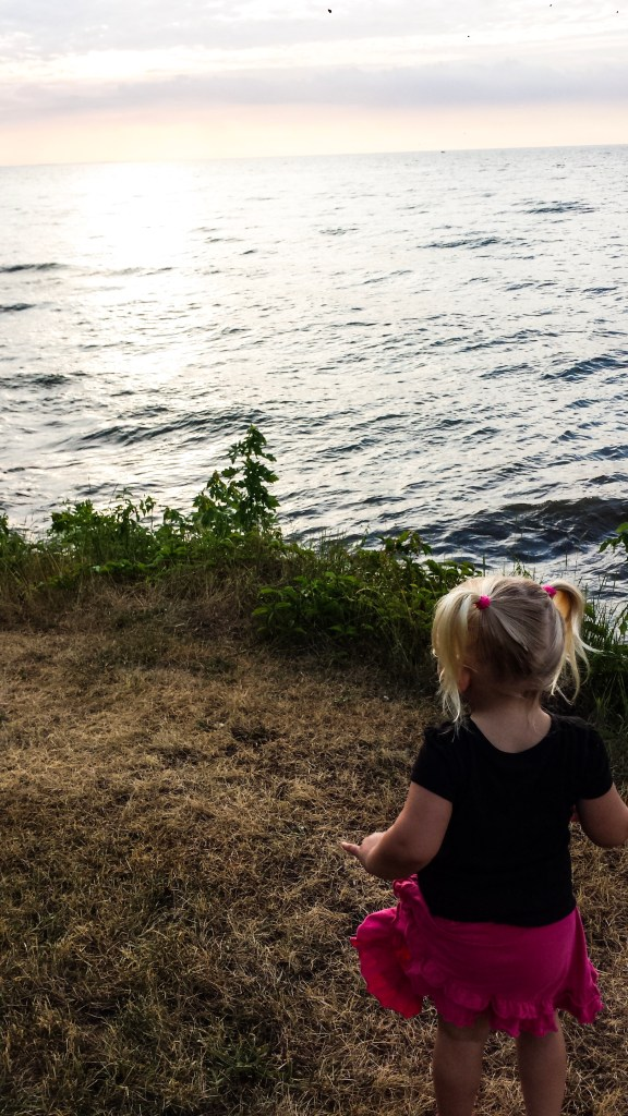 A little blonde girl stares at the lake. She faces away from the camera in What it's really like to travel with kids.
