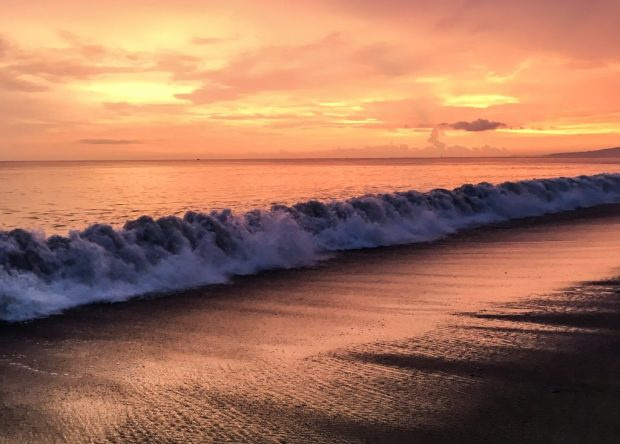 A wave from the Pacific Ocean is rolling in during the sunset in Puerto Vallarta.