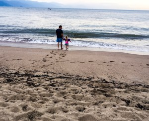 A father and daughter walk towards the surf of the Pacific Ocean.