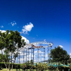 A far view of a roller coaster at Parque Bicentenario, with a deep blue sky at the backdrop.
