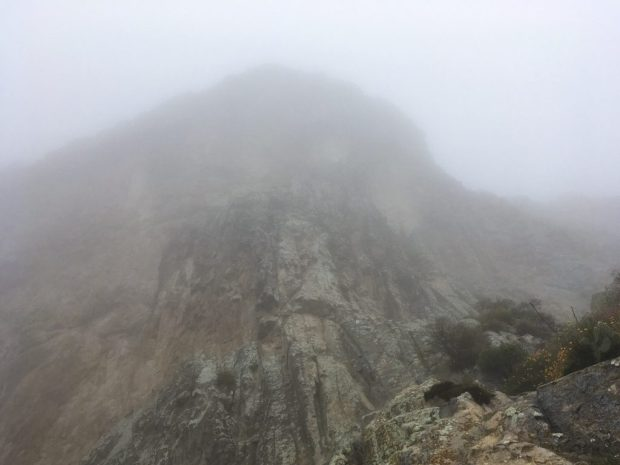 A Peña de Bernal shrouded in fog on a rainy Saturday.