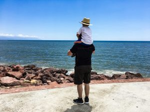 A boy sits on his father's shoulders and they are facing the Pacific Ocean.