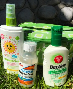 In the foreground, sunscreen, children's ibuprofen, and bactine. In the backround, green grass, gray rocks, and a green bag that I use as my first aid kit