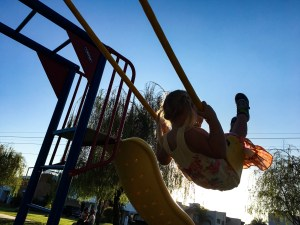 the silhouette of a girl swinging high on her swing.