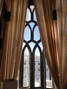 The gothic style windows with peach colored curtains.