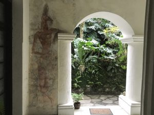 a mural on a wall, next to an open arch to the garden of the hotel.