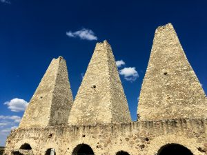 a graying trio of off-white stone towers made of stone, against a deep blue sky with few clouds at the Santa Brigida Mine