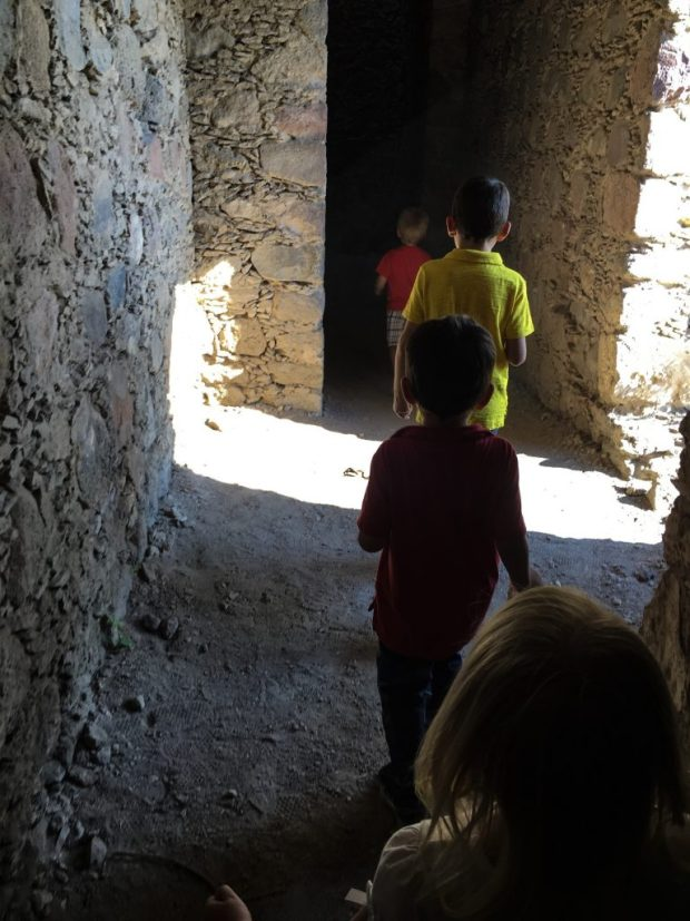 4 kids are running through a stone hallway of sorts. It's the ruins of an old mine that ceased operations in the 1960s in Mexico. Light from the opening on the right illuminates part of the path.