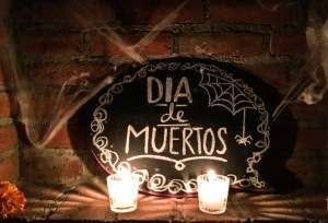 "a spooky sign covered with cobwebs that says ""Dia de Muertos."" In front sit two white, lit candles. This from our first Day of the Dead party."