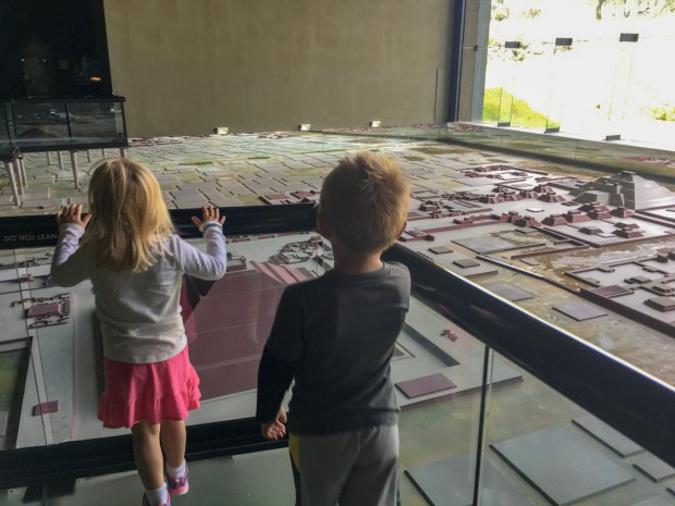 two children are on a bridge, looking over a model of the Teotihuacan site. In front of them is the Temple of the Sun and off to the far right is the Temple of the Moon.