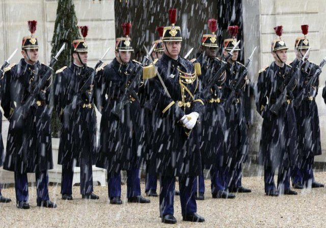Snowflakes fall as Republican Guards stand in formation in the courtyard of the Elysee Palace as French President Francois Hollande (not pictured) welcomes Poland's Prime Minister Ewa Kopacz (not pictured) in Paris, January 30, 2015. REUTERS/Philippe Wojazer (FRANCE - Tags: POLITICS ENVIRONMENT) - RTR4NKWM