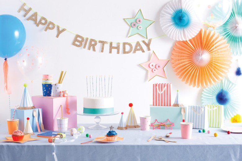 Birthday decorations and cake with happy birthday sign on the wall