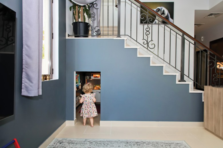 Child entering her play area under the stairs