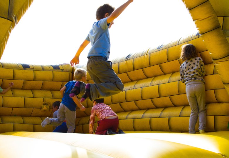 Children bouncing up and down on yellow bouncy castle
