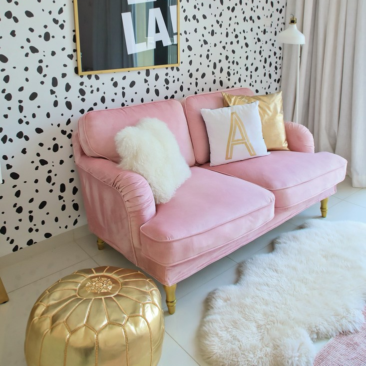 Pink sofa with painting behind