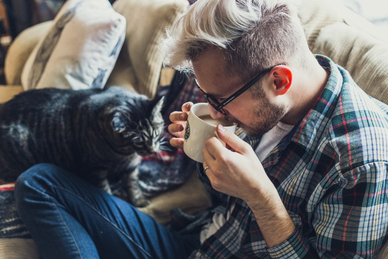 man wearing glasses drinking coffee with cat on lap on sofa
