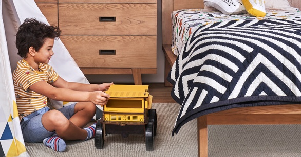 Boy plays with a toy truck Crate and Kids styled boys' bedroom