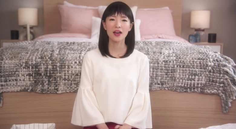 Marie Kondo sitting in front of bed on Netflix show