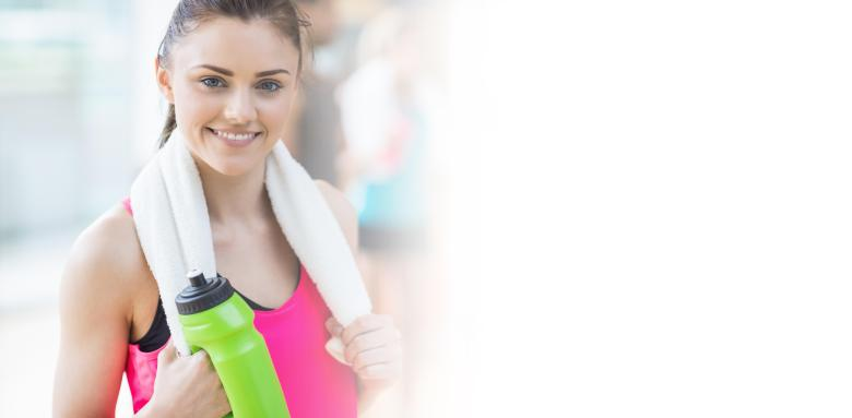 smiling woman with towel and bottle at gym