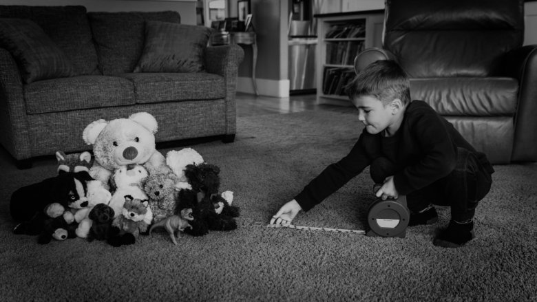 Little boy lines up teddy bears black and white