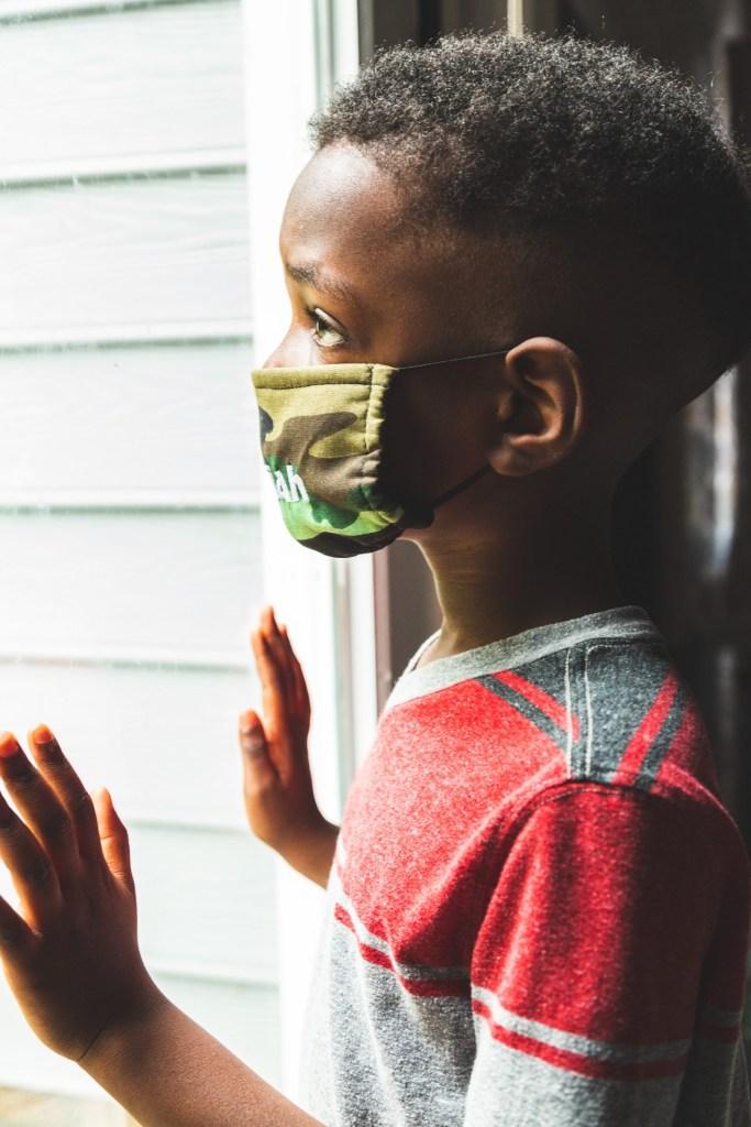 little boy wearing face mask looking out window