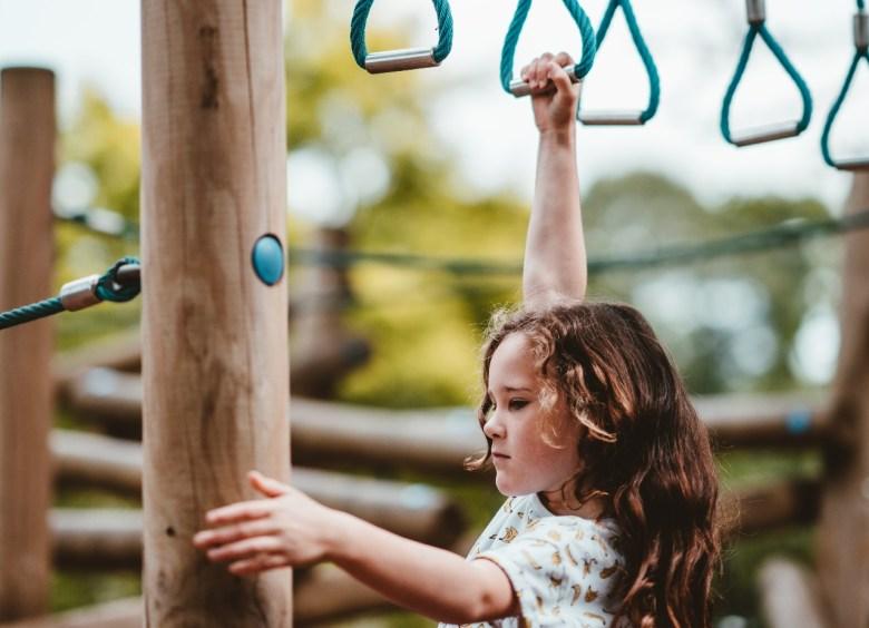 little girl swinging from monkey bars