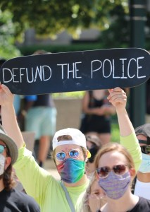 """A White man holding a sign that reads """"Defund the police."""""""