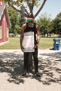 A Black man holds a BLM sign while standing in Victoria Park in London, ON.