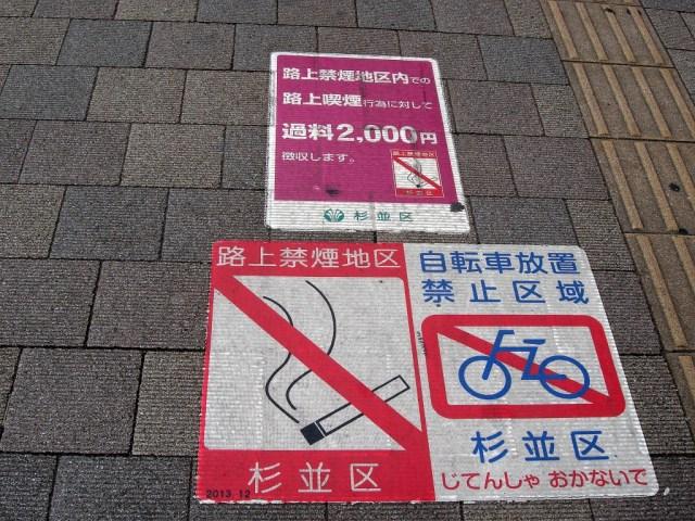 Cartells de prohibició de fumar al terra d'un carrer peatonal