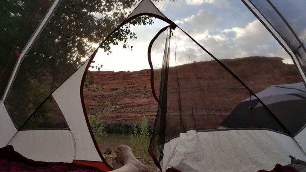 feet hanging from tent while camping in arches national park