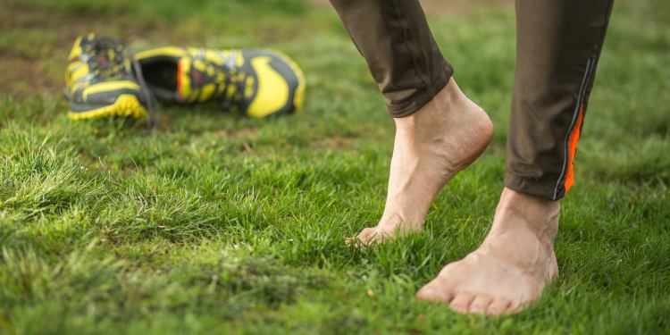 feet stretching on the grass after trail running