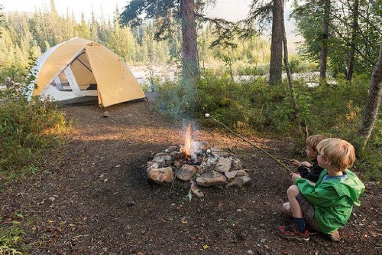 Kids roast smores by a fire near a yellow tent at ophir creek in alaska