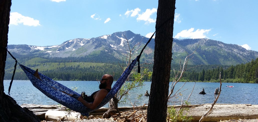 a man rests in a hammock near an alpine lake