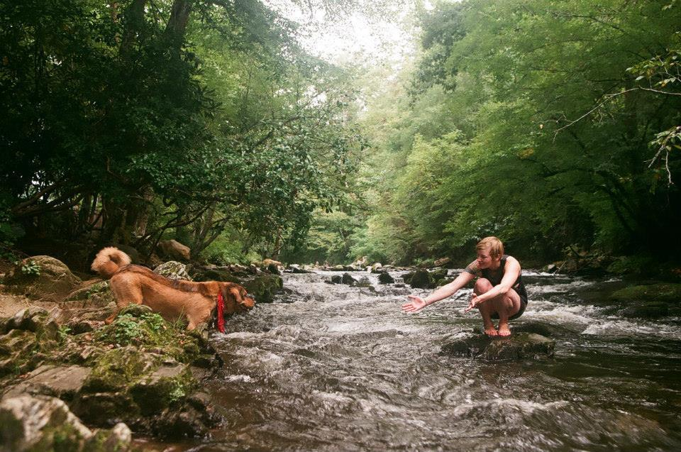 woman kneels on a rock in a river as she holds her arms out for a running dog