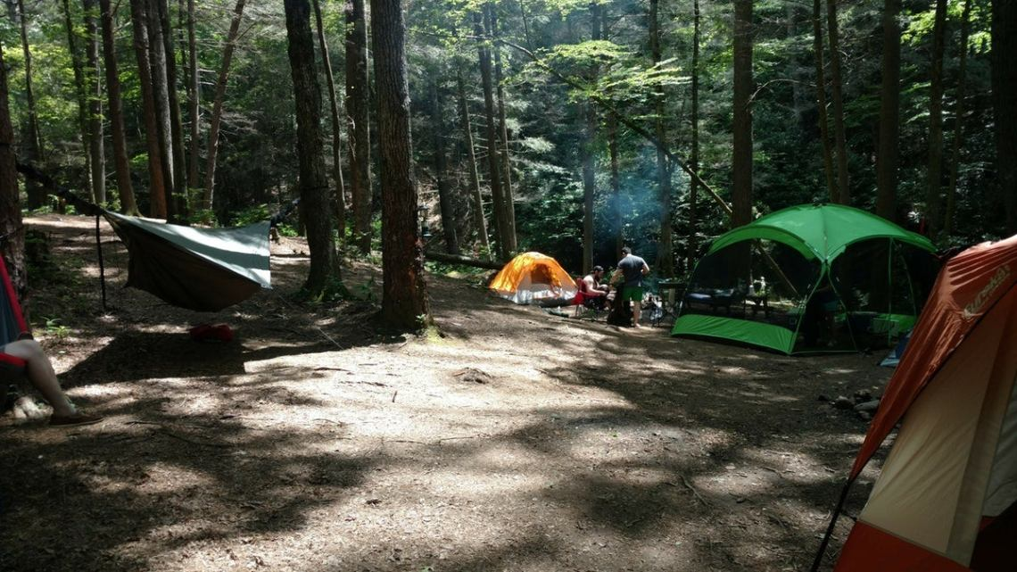 orange and green tents adorn a campsite setup at raven cliff falls campground