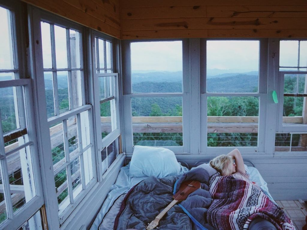 visitor sleeping in the fire tower with panoramic views out every window
