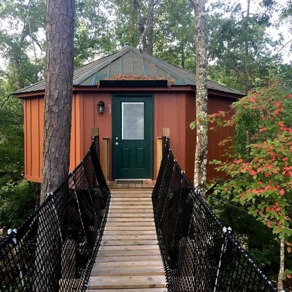bridge leading to wooded rust colored yurt