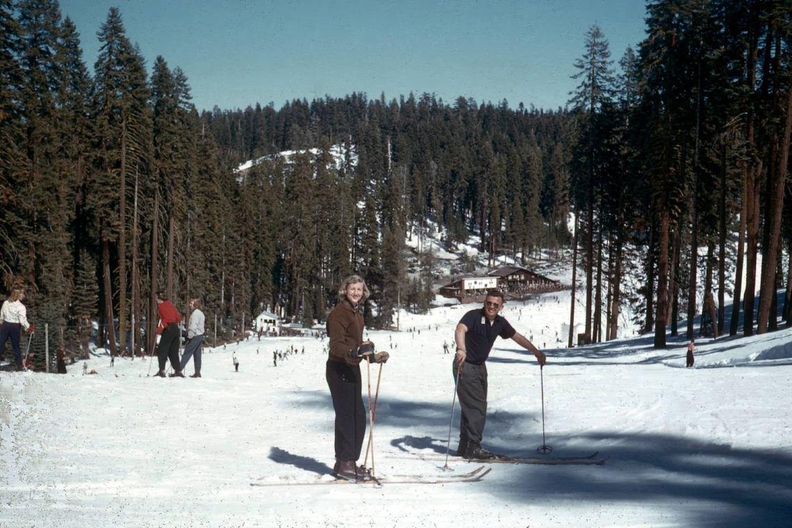 vintage photo of skiers in the foreground with a lodge in the background, badger pass circa 1950
