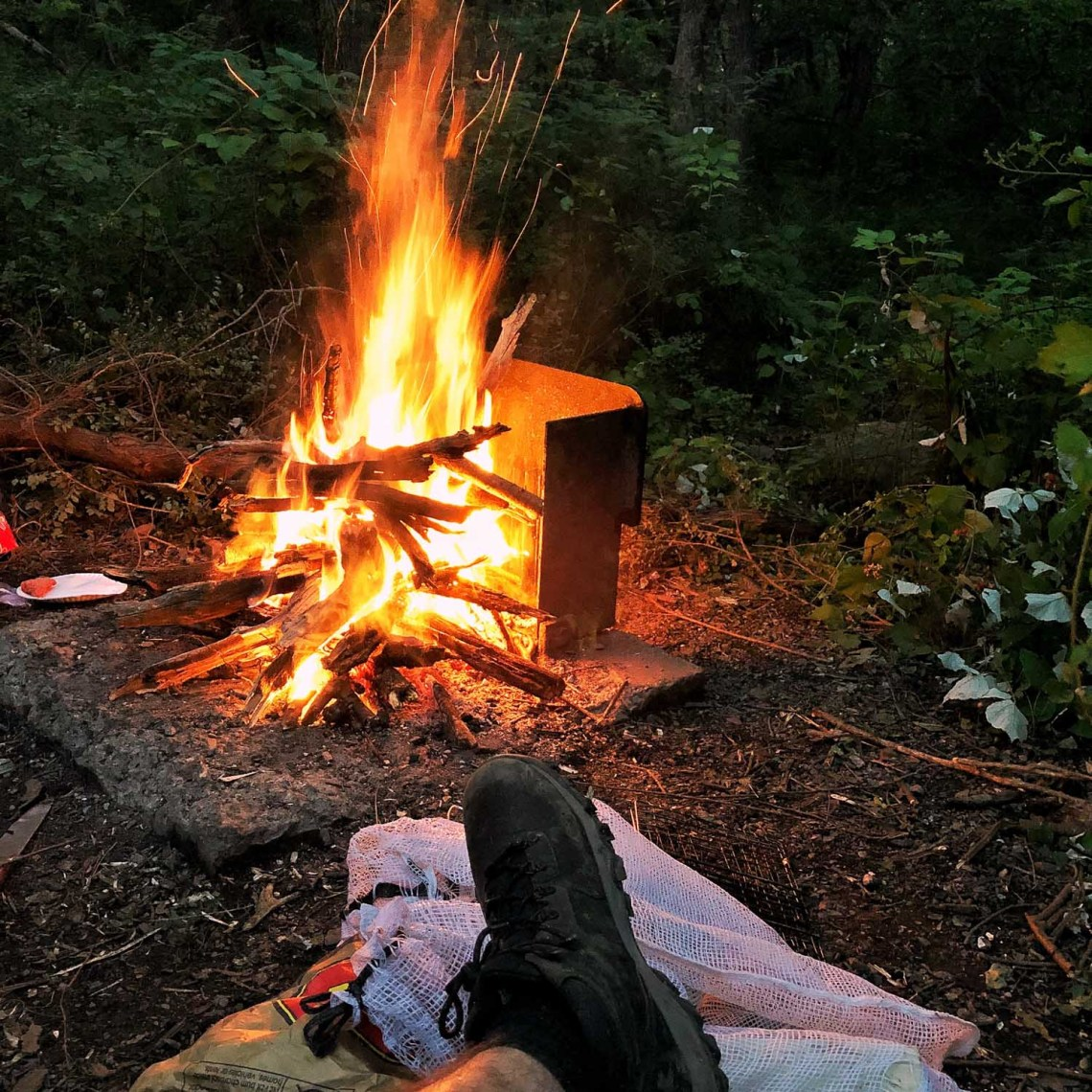 Camper resting foot on sack of potatoes in front of campfire at Loft Mountain Campground